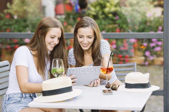 Два молодих подруг дивлячись на цифровий планшет на тротуарі кафе — стокове фото