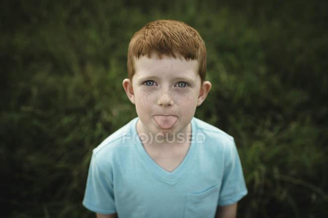 Retrato de menino de cabelos vermelho saindo da língua — Fotografia de Stock