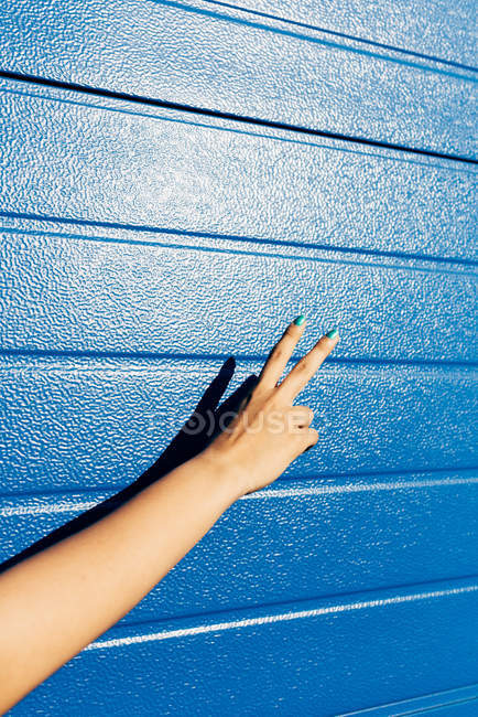 Cropped image of woman showing peace symbol near blue wall — Stock Photo