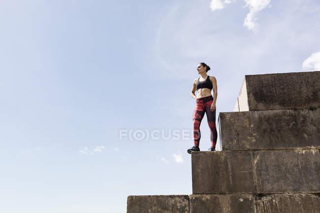 Молода жінка безкоштовно бігун дивлячись з вершини хвилерізи — стокове фото