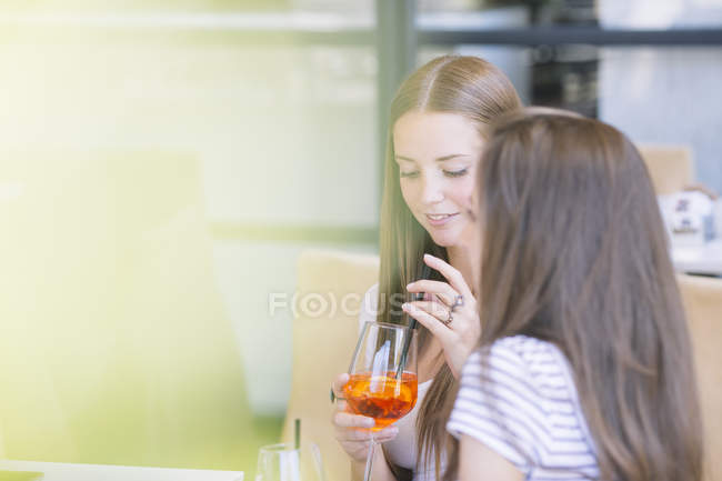 Two young female friends drinking cocktails at sidewalk cafe — Stock Photo