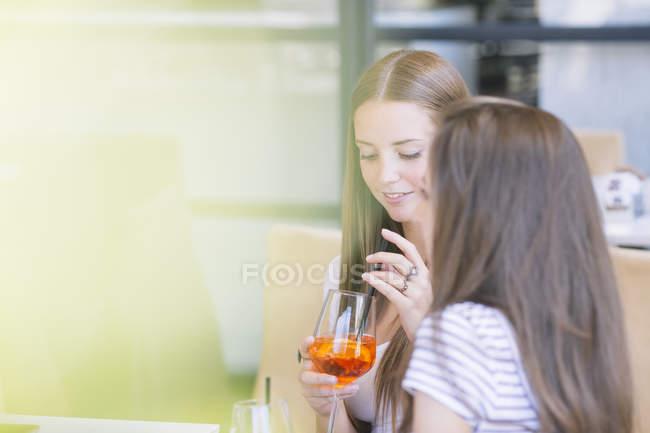 Dois jovens amigos femininos beber cocktails no café de calçada — Fotografia de Stock