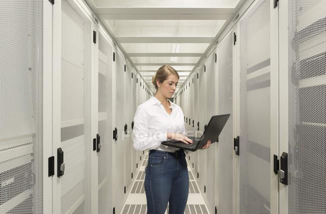 Porträt einer jungen Frau im Rechenzentrum mit Laptop — Stockfoto