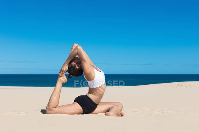 Side view of woman stretching on beach — Stock Photo