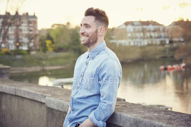 Bearded man leaning against bridge over River Thames, Richmond, UK — Stock Photo