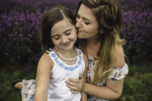 Mother kissing daughter in lavender field — Stock Photo