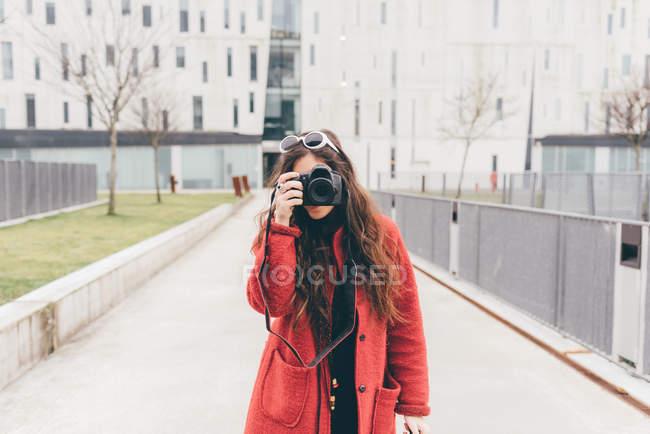 Портрет молодої жінки, дивлячись через видошукач камери — стокове фото