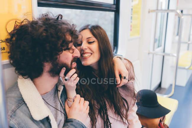 Молода пара, сидячи в метро поїзд, пустувати, жінка, хапаючи людини підборіддя — стокове фото