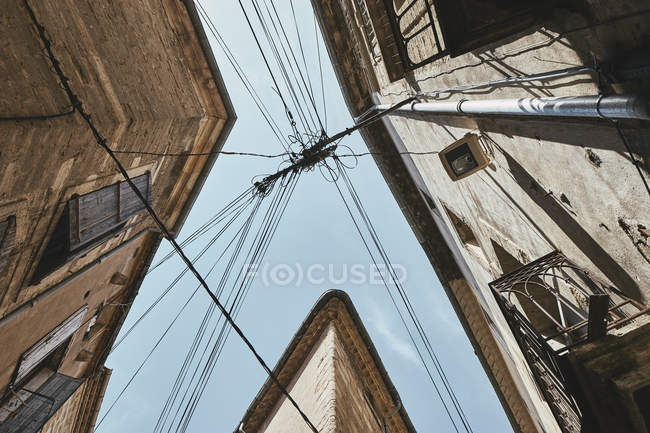 Vue en angle bas des bâtiments traditionnels et des lignes électriques contre le ciel bleu, Pezenas, région Occitanie, France — Photo de stock