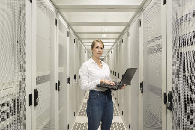 Portrait of young woman in data center using laptop — Stock Photo