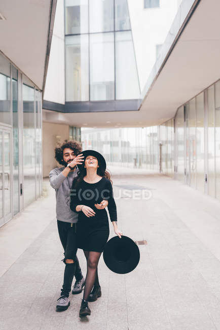 Young couple walking in urban environment, fooling around, laughing — Stock Photo