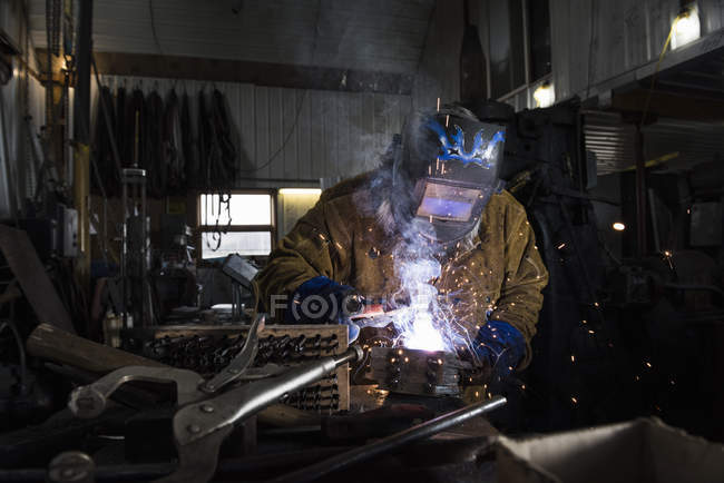Blacksmith in welding mask working with metal in workshop — Stock Photo