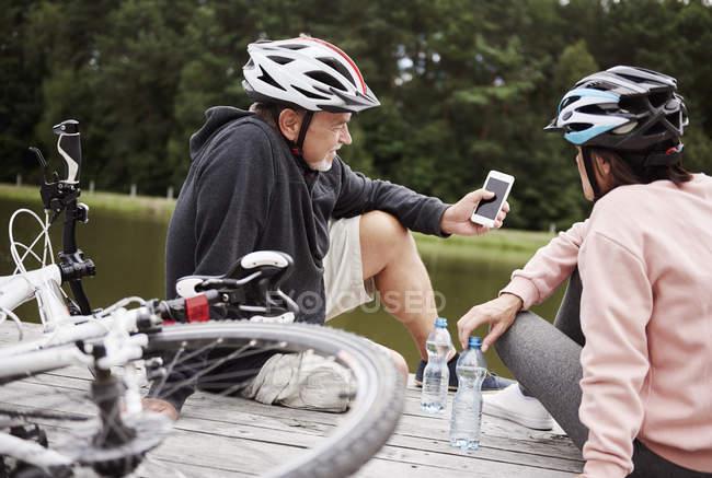 Літня пара в шоломи дивлячись на смартфон на пристані — стокове фото