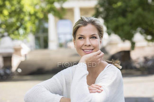 Портрет женщины с подбородком в руке, смотрящей в сторону и улыбающейся — стоковое фото