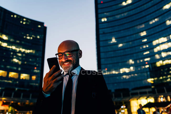Hombre de negocios maduro usando smartphone por la noche - foto de stock