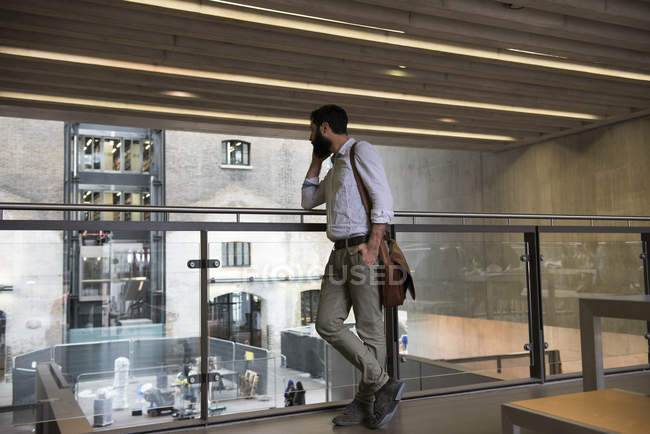 Man in office building making smartphone call — Stock Photo