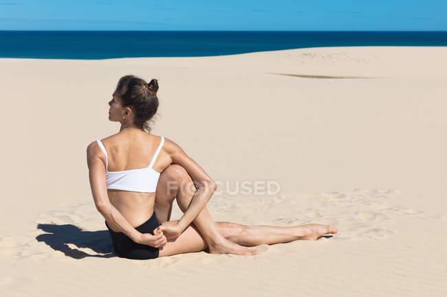 Вид сбоку женщины на пляже в позе йоги — стоковое фото