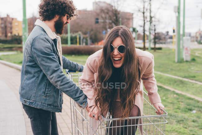 Молода пара на вулиці, людина штовхає жінка вздовж покупки візки в — стокове фото