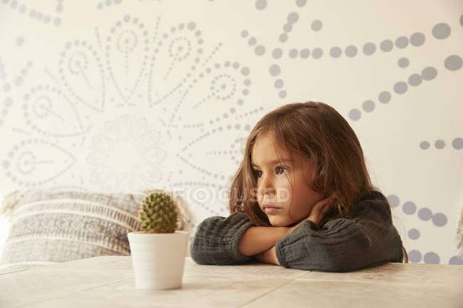 Young girl sitting at table, resting head on arms, pensive expression — Stock Photo