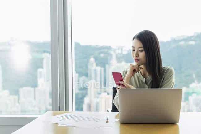 Бизнесвумен, использующая ноутбук и смартфон — стоковое фото