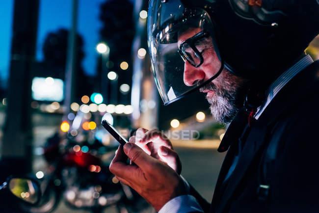 Homme d'affaires mature en casque de moto en utilisant un smartphone — Photo de stock