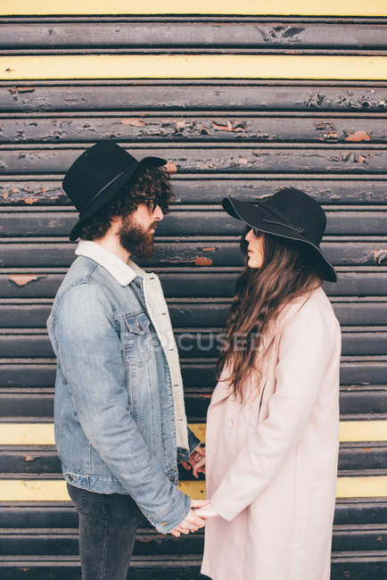 Portrait of young man and woman, face to face, holding hands, pensive expressions — Stock Photo