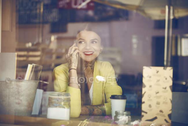 Junge Frau sitzt im Café, benutzt Smartphone, Tätowierungen auf der Hand, Blick durch Café-Fenster — Stockfoto