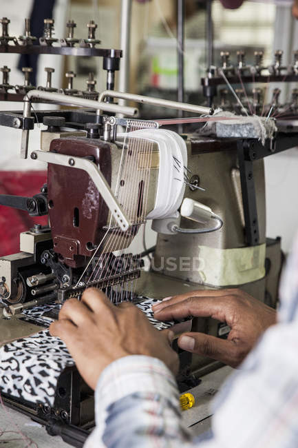 Persona que trabaja en la máquina de coser industrial smocking en fábrica, Ciudad del Cabo, Sudáfrica - foto de stock