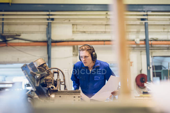 Factory worker wearing protective clothing, inspecting manufacturing machine part — Stock Photo