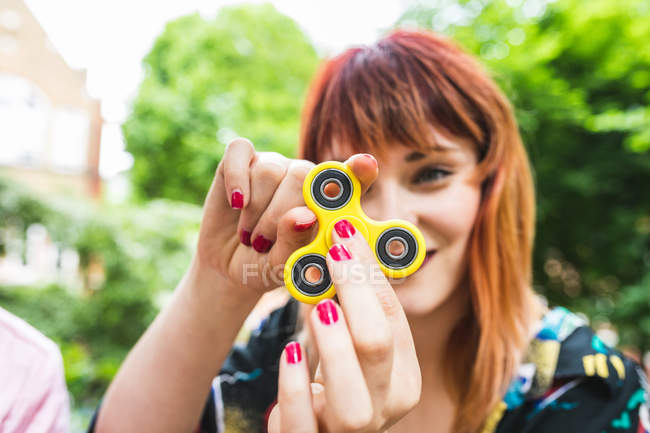 Young woman playing with fidget spinner in park — Stock Photo