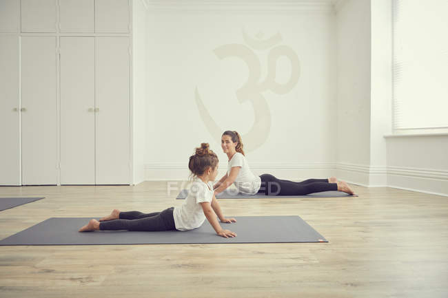 Mother and daughter in yoga studio, in yoga positions — Stock Photo