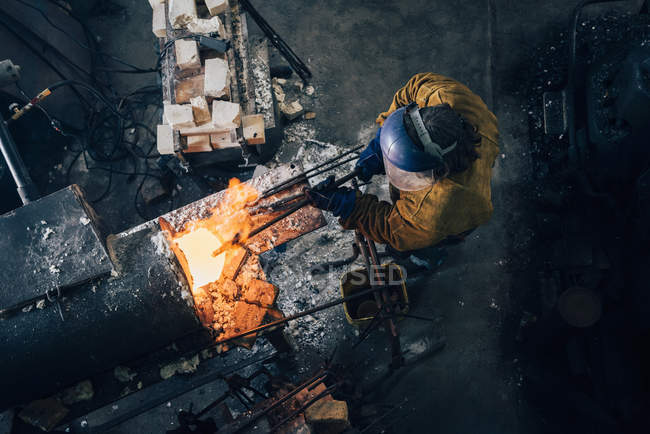 Overhead view of blacksmith shaping red hot metal rod in workshop furnace — Stock Photo