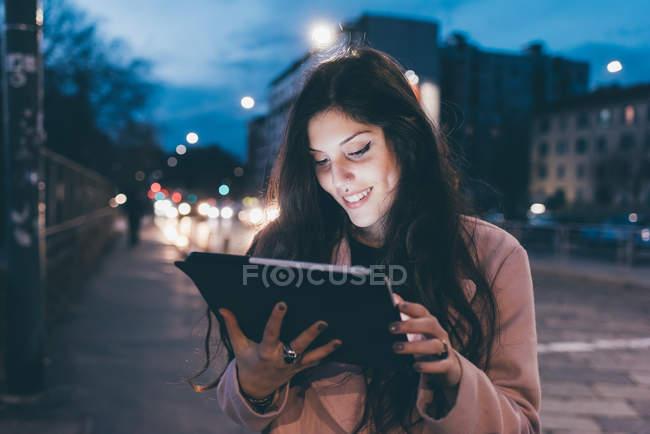 Junge Frau, im Freien, nachts, Blick auf digitales Tablet, Gesicht beleuchtet — Stockfoto