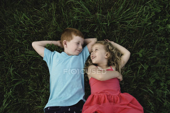 Overhead portrait of boy and sister lying on grass looking at each other — Stock Photo