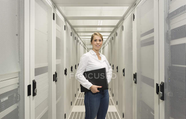 Portrait of young woman in data center holding laptop — Stock Photo