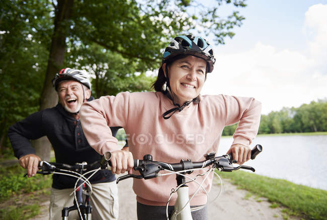 Mature couple laughing and cycling beside lake — Stock Photo