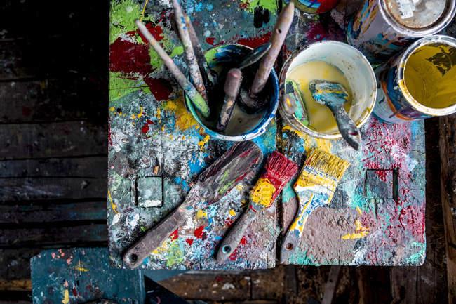 Pinceles y macetas de pinturas en la mesa del taller - foto de stock