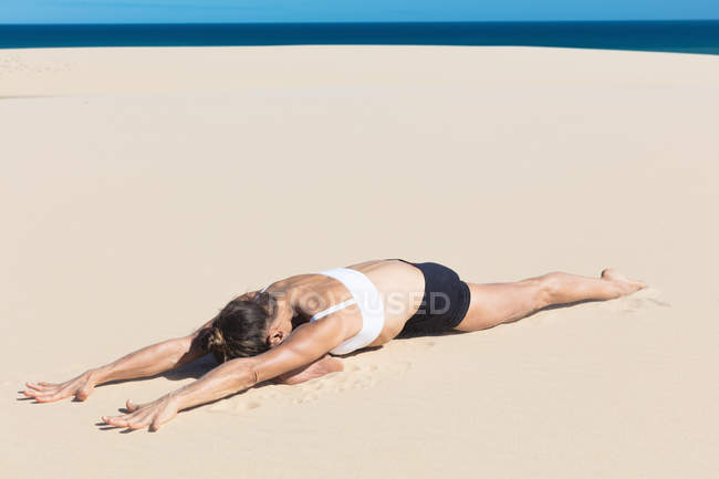 Woman on beach lying on front in yoga position — Stock Photo