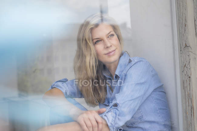 Ritratto di donna che guarda attraverso il vetro della finestra — Foto stock