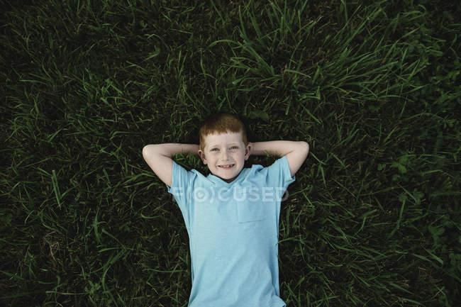 Портрет рыжеволосого мальчика на траве — стоковое фото