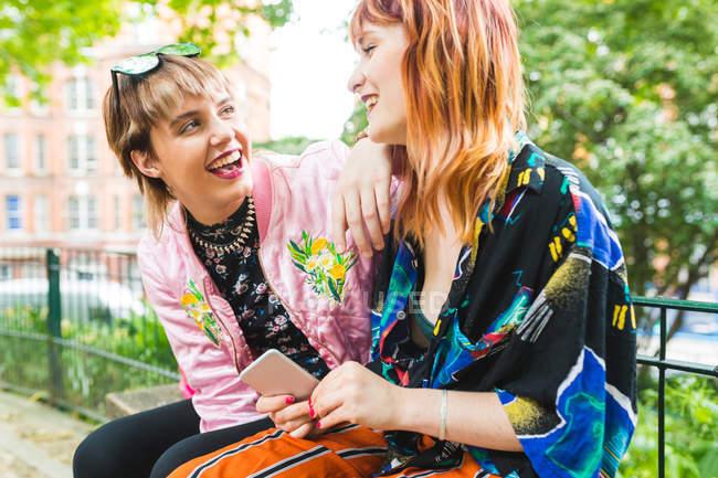 Два ретро стилі молодих жінок, сміючись в парку — стокове фото