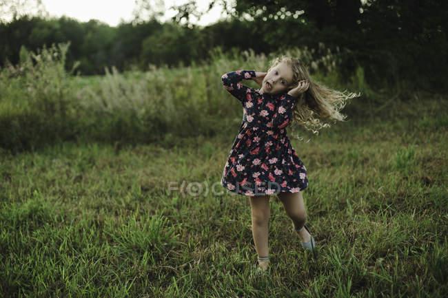 Loira de cabelos menina correndo e puxando um rosto no campo — Fotografia de Stock