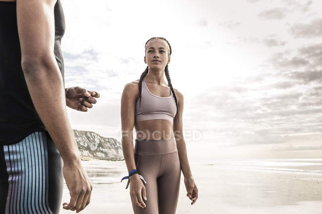 Young female runner looking at young man on beach — Stock Photo