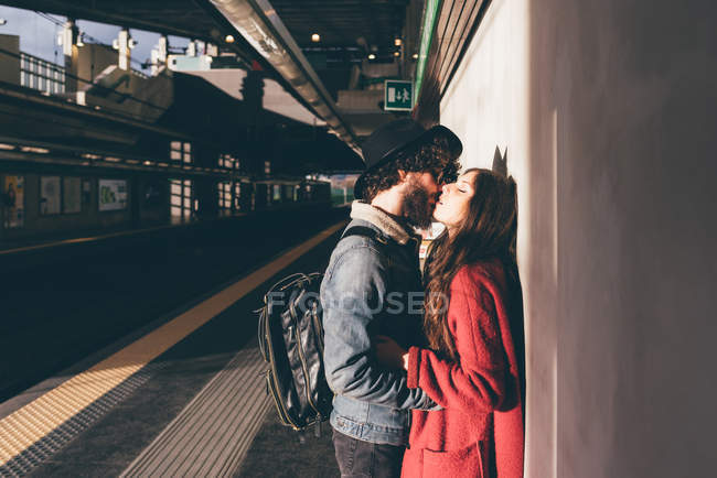 Jeune couple debout sur le quai du train, embrasser — Photo de stock