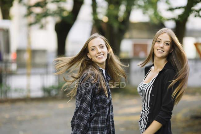Ritratto di due giovani amiche che vorticano lunghi capelli castani nel parco — Foto stock