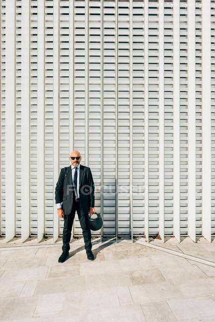 Portrait of mature businessman outdoors, holding motorcycle helmet — Stock Photo