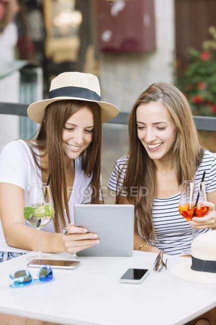 Две юные подруги смотрят на цифровые планшеты в кафе на тротуаре — стоковое фото