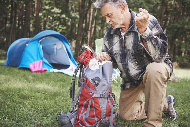 Senior man near tent packing backpack — Stock Photo