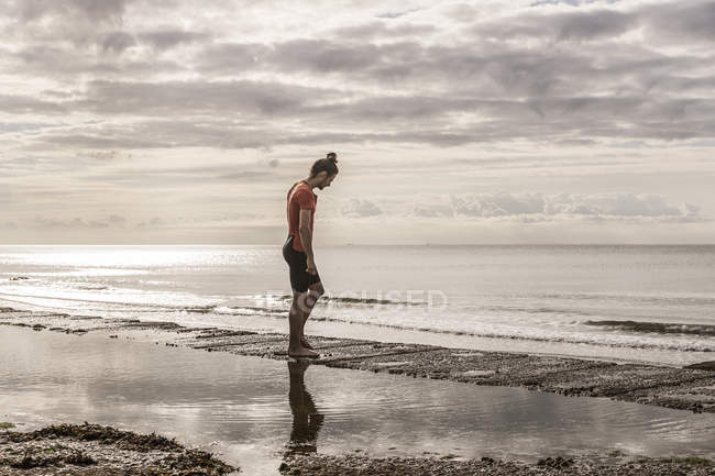 Side view of man on shoreline looking at sea — Stock Photo