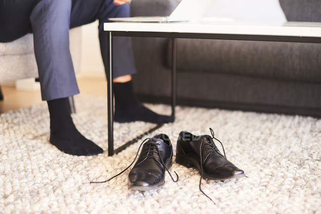 Man feet and shoes in living room — Stock Photo